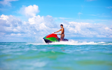 joyful man riding jet ski, tropical ocean, active vacation