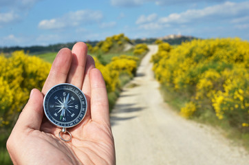 Compass in the hand against rural road Wall mural