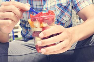 youn man eating a fruit salad outdoors