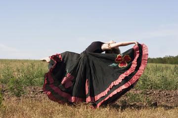 Young woman dancing outdoors in long skirt