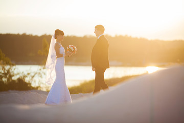 Groom and bride is posing on the background beautiful sunset on
