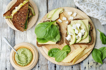 grilled rye sandwiches with cheese, spinach, pesto, avocado and