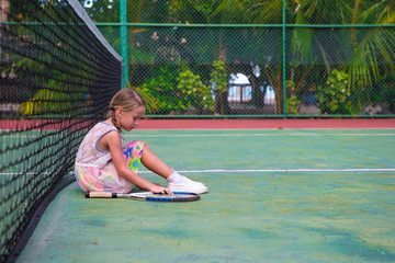 Little girl trying to play tennis on outdoor court