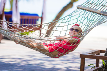 Cute little girl on tropical vacation relaxing in hammock