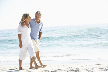Senior Couple On Holiday Walking Along Sandy Beach