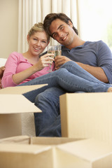 Young Couple Moving Into New Home Celebrating With Champagne