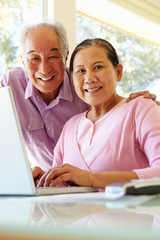 Senior Taiwanese couple working on laptop