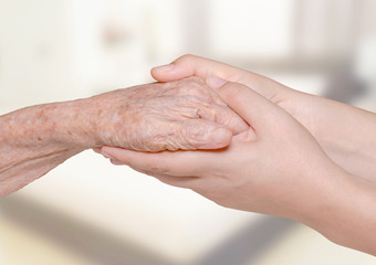 Young woman holding her grandma hand in bedroom