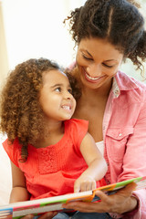 Mixed race woman and daughter reading