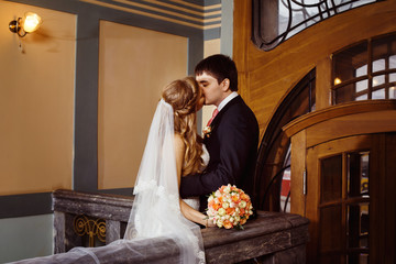 Beautiful wedding couple is kissing in classic vintage interior