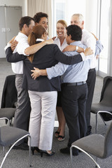 Group Of Businesspeople Bonding In Circle At Company Seminar