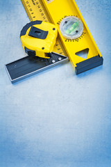 Tape measure construction level and square ruler on metallic bac