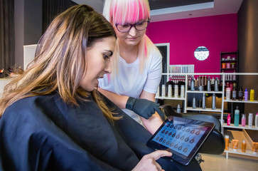 Woman looking with hairdresser hair dye palette in a tablet