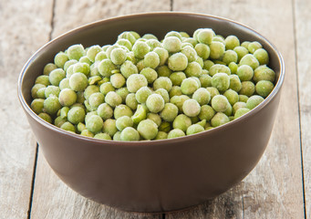 Fresh frozen peas in bowl close up