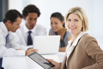 Portrait Of Female Executive Using Tablet Computer With Office Meeting In Background