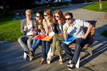 group of happy students eating green apples