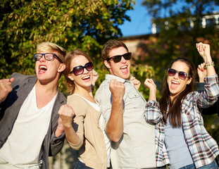 group of happy friends showing triumph gesture