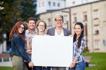 happy teenage students holding white blank board