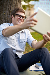happy teenage boy with tablet pc taking selfie