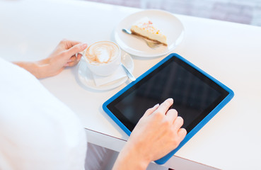 close up of woman with tablet pc drinking coffee
