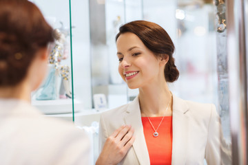 happy woman choosing pendant at jewelry store
