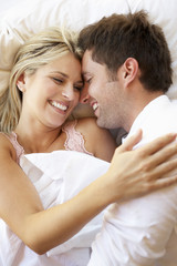 Couple Relaxing In Bed