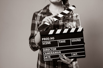 Close-up of a girl with a movie clapper.