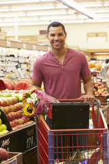 Man Pushing Trolley By Fruit Counter In Supermarket
