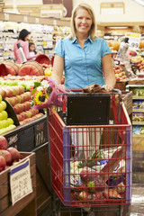 Woman Pushing Trolley By Fruit Counter In Supermarket
