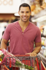 Man Pushing Trolley By Produce Counter In Supermarket