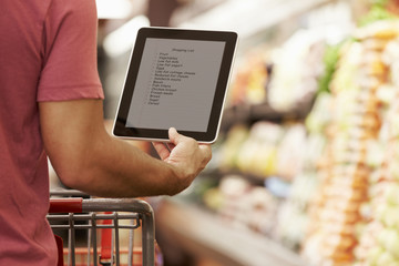 Close Up Of Man Reading Shopping List From Digital Tablet In Supermarket