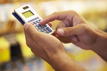 Man In Grocery Aisle Of Supermarket Using Calculator