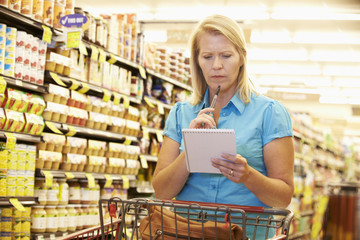 Woman In Grocery Aisle Of Supermarket With List