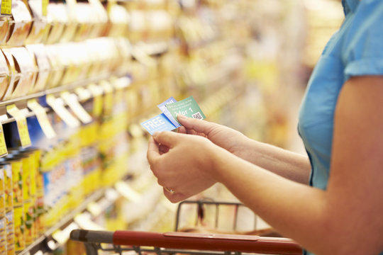 Woman In Grocery Aisle Of Supermarket With Coupons