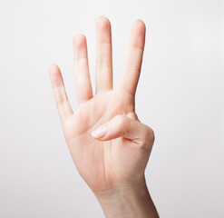 Female hand is showing four fingers isolated on white background