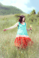 Hippie girl picking flowers in the meadow