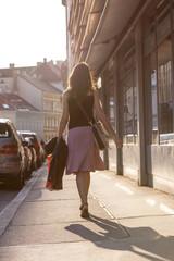 Urban girl striding through a city street on a sunny day