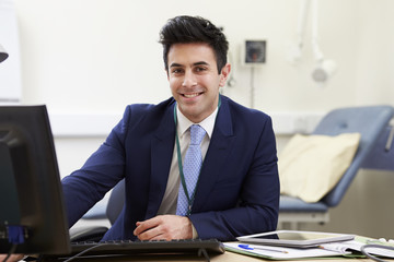 Portrait Of Male Consultant Working At Desk