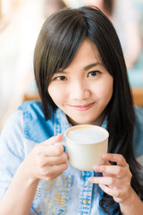 Happy asian young woman sitting in vintage cafe with cup of coff