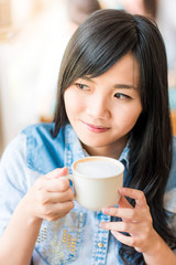 Beautiful cute girl in the cafe with white coffee cup