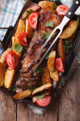homemade food: pork, potatoes and tomatoes on a pan. vertical top view