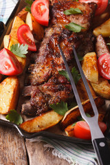 BBQ pork, potatoes and tomatoes on a grill pan. vertical top view