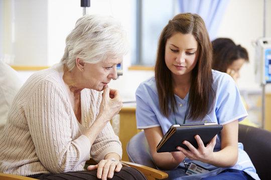 Woman Having Chemotherapy With Nurse Using Digital Tablet