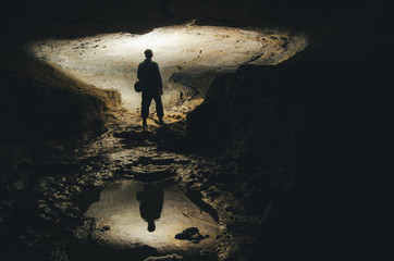 man silhouette reflecting in water in dark cave