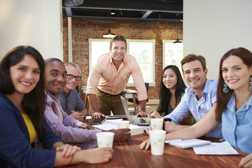 Portrait Of Male Boss With Team In Meeting