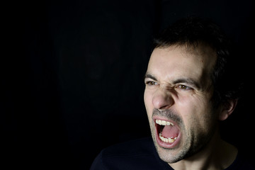 shouting angry young man, black background