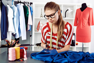 Young clothing designer making patterns of fabric in studio