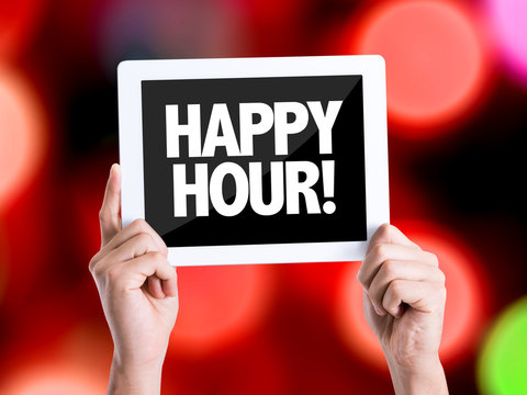 Tablet pc with text Happy Hour with bokeh background