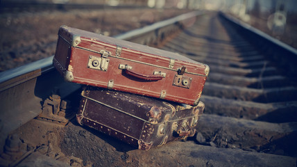 The image of vintage suitcases thrown on railway rails.