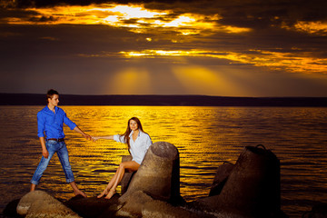 Beautiful young woman is holding her man by hand at sea sunset